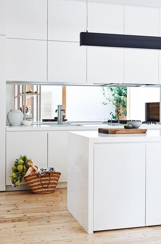 Bancada de cozinha em espelho que reflecte as grandes janelas