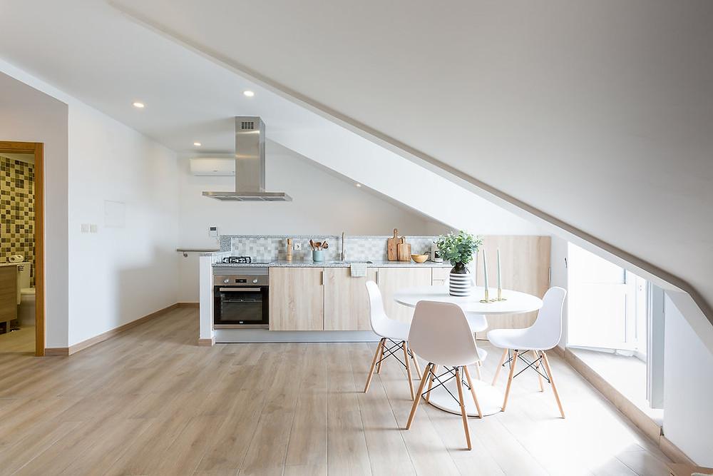 cozinha moderna em águas furtadas, com mesa redonda branca e 4 cadeiras