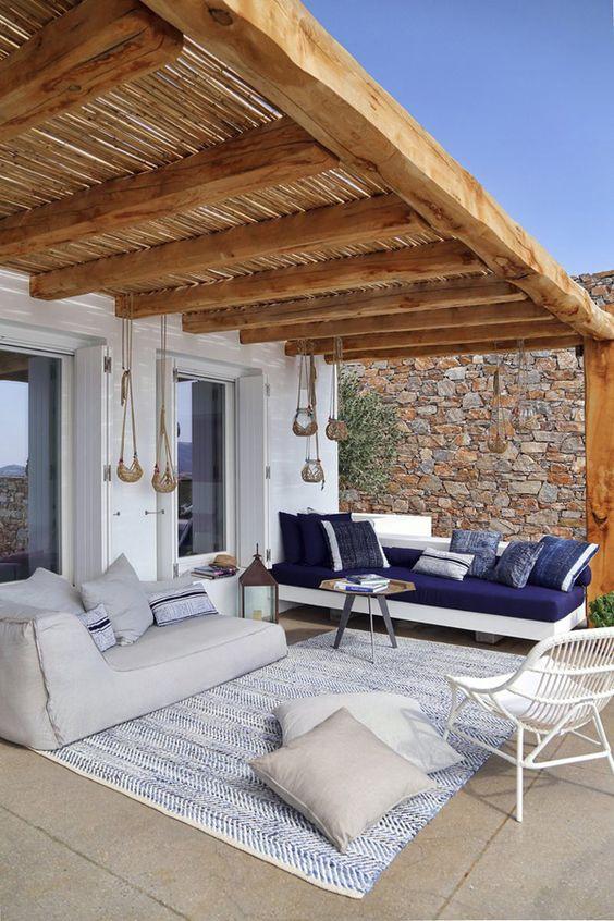 páteo exterior de uma casa térrea, coberto com uma estrutura de madeira e palha. Com dois sofas grandes brancos e almofdas azuis. Grande tapete em tons de azul e branco com duas almofadas no chão. Cadeira de verga branca