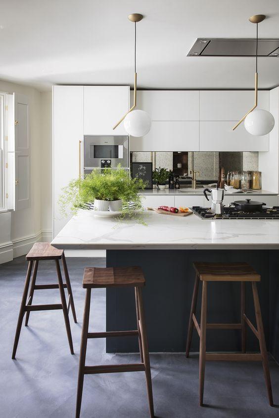 Cozinha moderna com aplicação de espelho entre bancadas aumenta a sensação de profundidade.