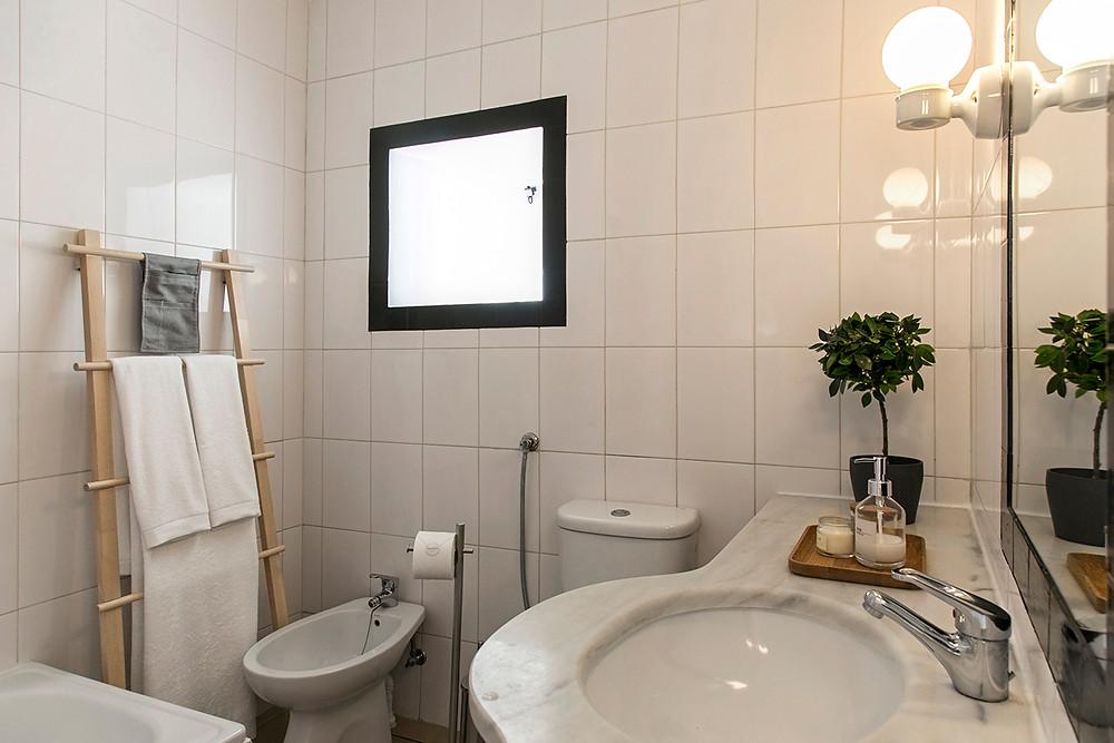 casa de banho branca com toalheiro de pé de madeira