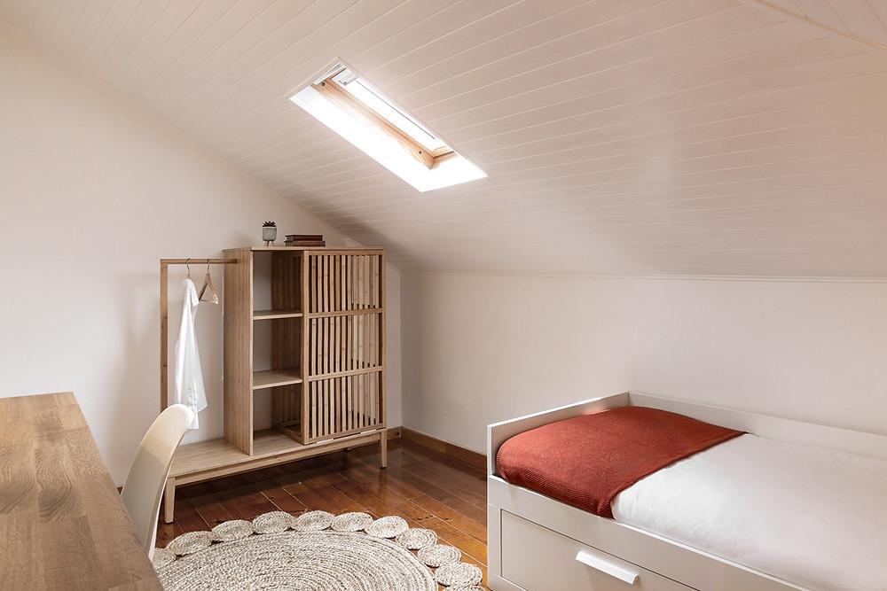 Quarto com tecto esconso de madeira branca com roupeiro leve e moderno em madeira de carvalho