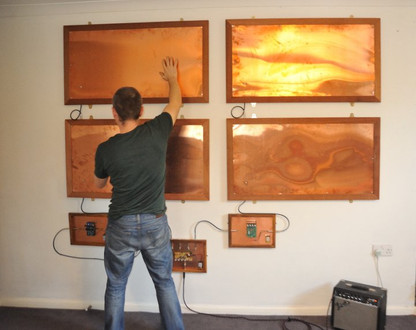 Wall hung copper based artwork made nice by touching