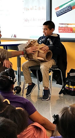 Student playing music on a drum