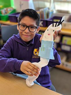 Student holding up his sock puppet he made