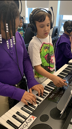 Students helping each other play notes on the keyboard