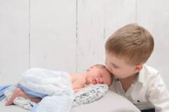 Neugeborenenshooting Geschwister Bruder Kuss.jpg