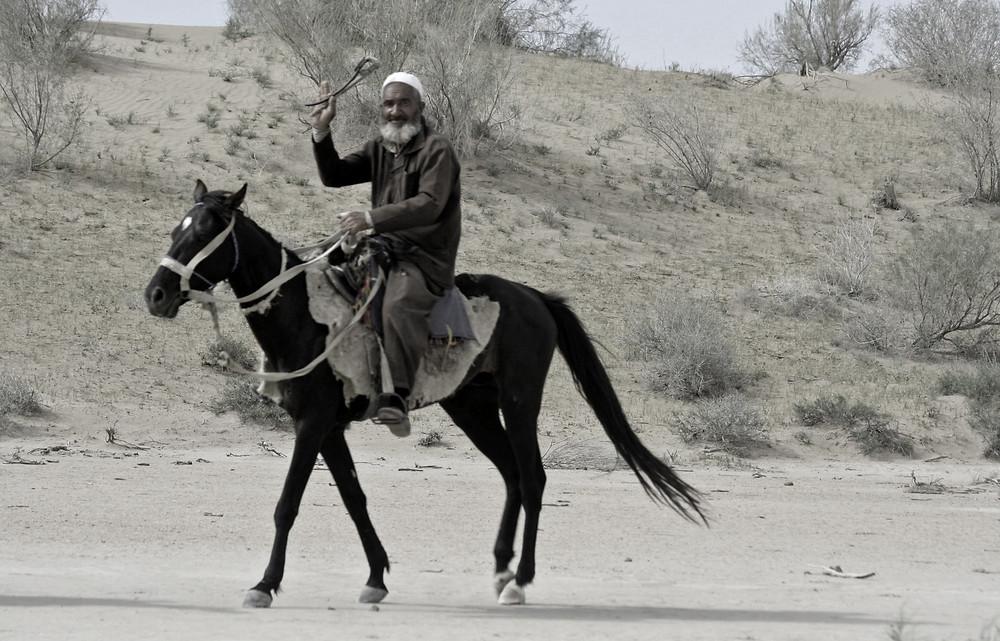 """Cavaliere che saluta in pieno Karakum desert, il temibile deserto dalle """"sabbie nere""""."""