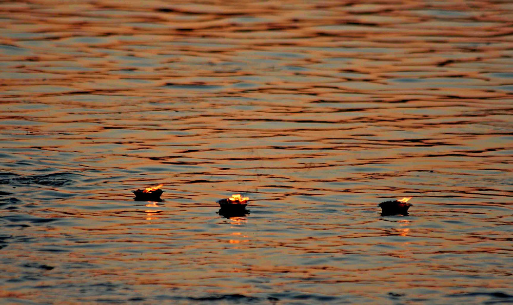 Lumini di canfora sul fiume Gomati al tramonto  (Dwarka, Gujarat – India, novembre 2018)