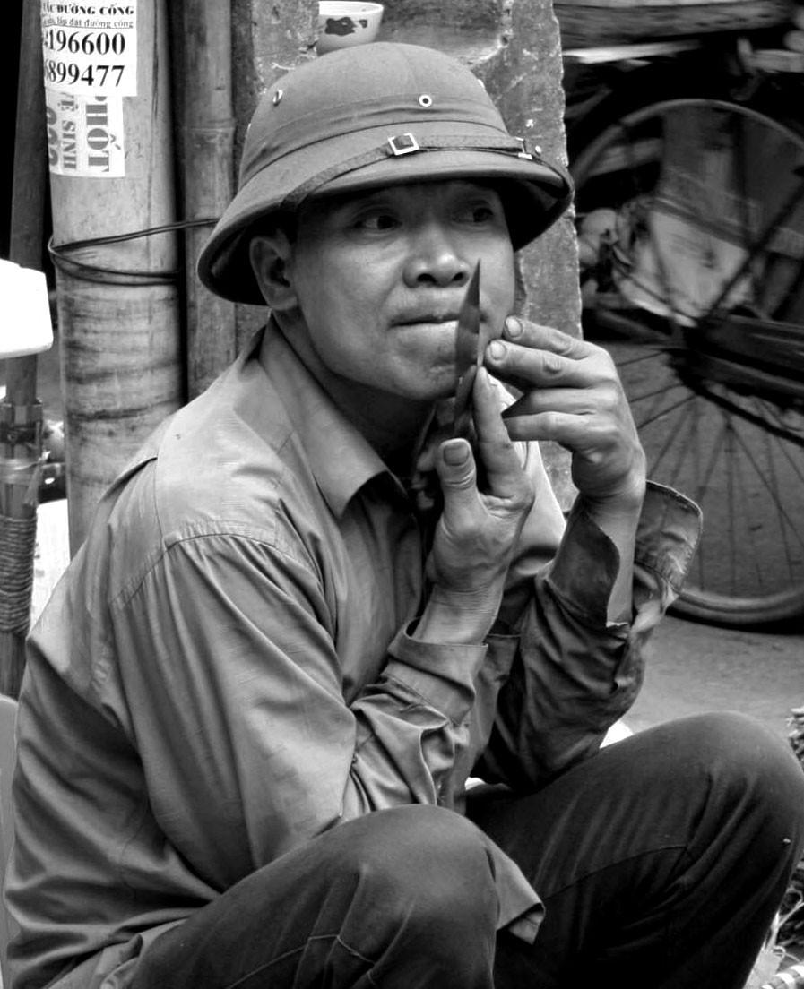 Uomo che si fa la barba per le strade di Hanoi (Vietnam, marzo-aprile 2009)