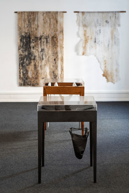"""View of the exhibition """"With a Handful of Dust"""" by Rita Gaspar Vieira, 2020. © Eduardo Sousa Ribeiro, 2020 1st Anachronistic Plan, 2020 Acrylic glass, pine wood table covered with graphite and replica of a graphite filter found at the Viarco Pencils 83 x 60 x 60 cm 2ºPlan Anachronistic, 2020 Acrylic glass, pine wood table, cotton paper manufactured on artist's atelier tables and pencils from the Viarco Pencil Factory 83 x 60 x 60 cm 3rd Plane Left: With the hand full of dust - table, 2018 Cotton paper manufactured on a work table from the Viarco Pencil Factory and turned support in chameleon wood 260 x 102 cm Right: With a hand full of dust - almost table, 2018 Manufactured cotton paper on a work table of the Viarco Pencil Factory and turned support in chameleon wood 240 x 102 cm"""