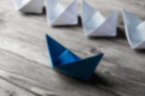 Set of origami boats on wooden table.jpg