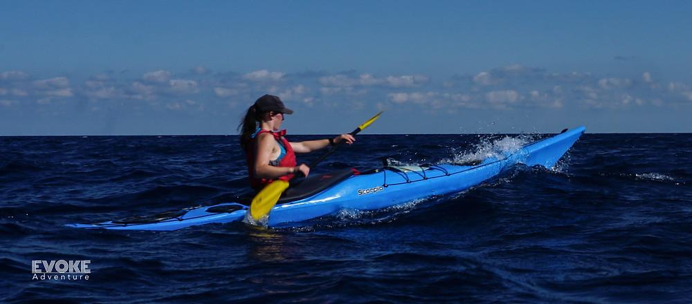 Holly paddling her sea kayak through rough water in Menorca.