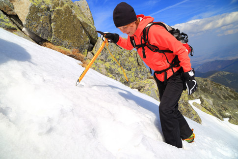 Climber woman ascends steep slope on the