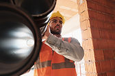 Construction worker with vest and hard hat carrying large pipe