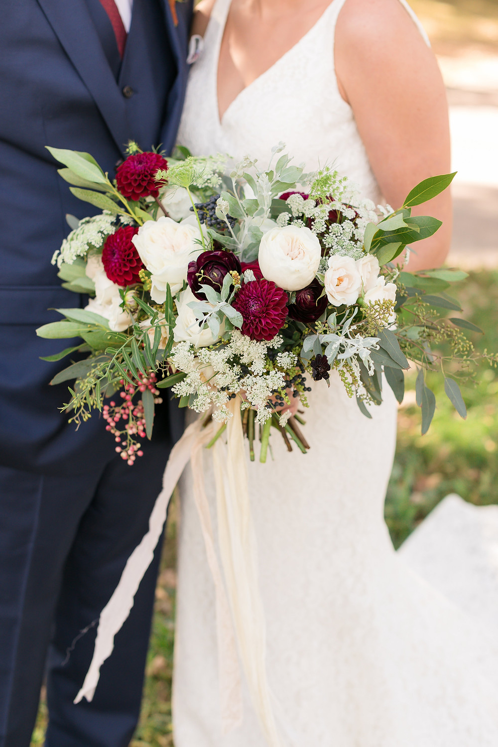 Lush bridal bouquet by studio bloom iowa with burgundy dahlias and white garden roses for a wedding at rapid creek cidery