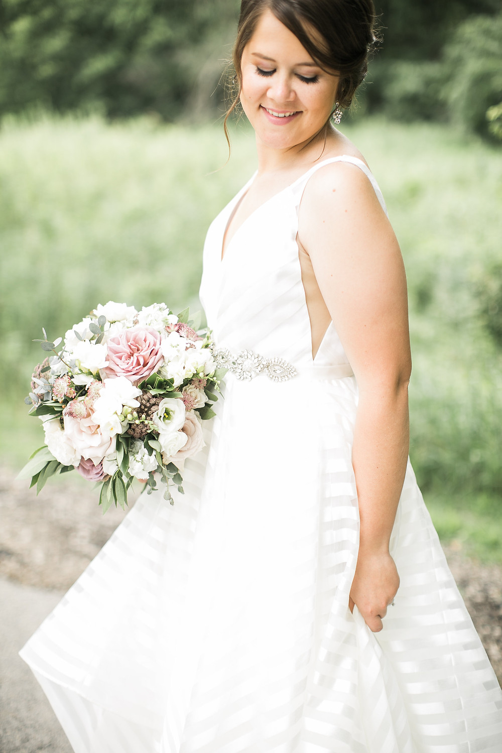 bride in striped wedding dress with mauve and white bridal bouquet of roses, ranunculus, and freesia by studio bloom iowa