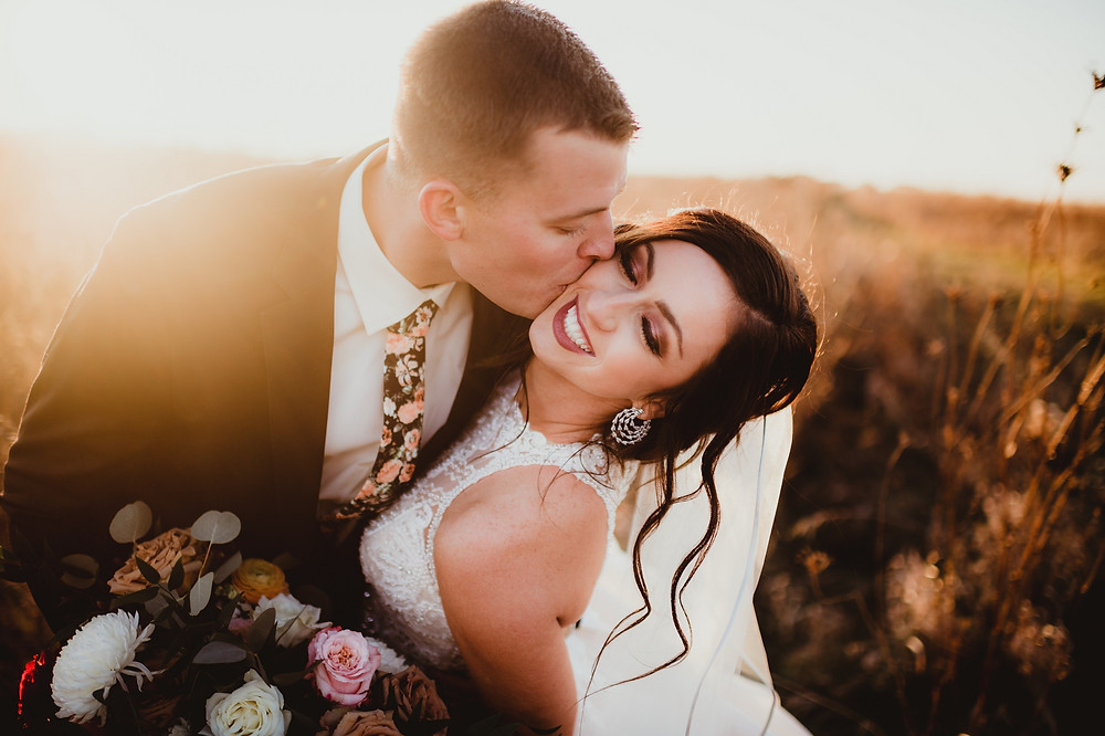 groom wearing peach and black floral tie kissing bride on the cheek in field at sunset