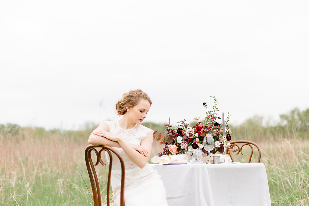bride sitting at table in grass prairie with flower centerpiece in burgundy and blush by studio bloom iowa wedding florist