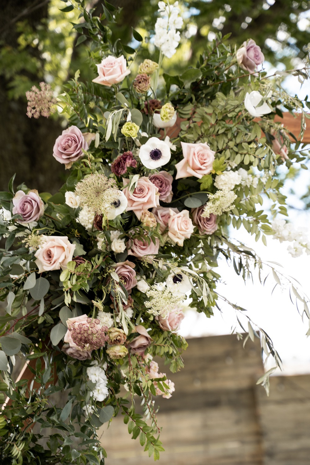 detail of wedding arch flowers in mauve and blush by Studio Bloom Iowa with roses, anemone, and lisianthus
