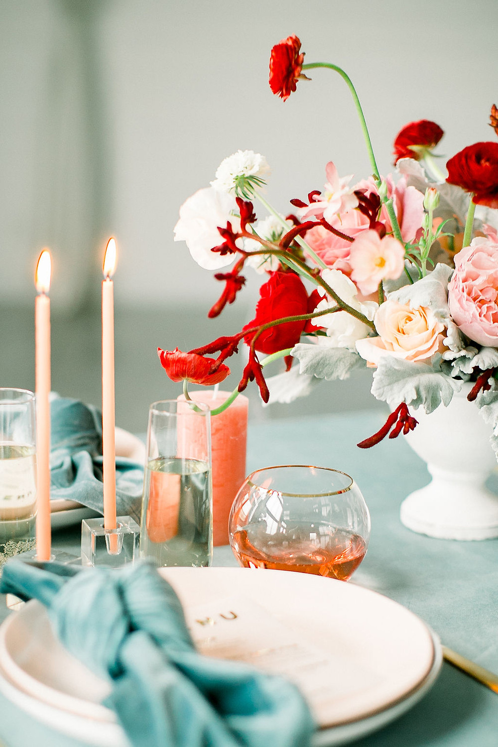 Red and blush centerpiece by Studio Bloom Iowa wedding florist in with garden roses, ranunculus, and sweet pea on dinner table