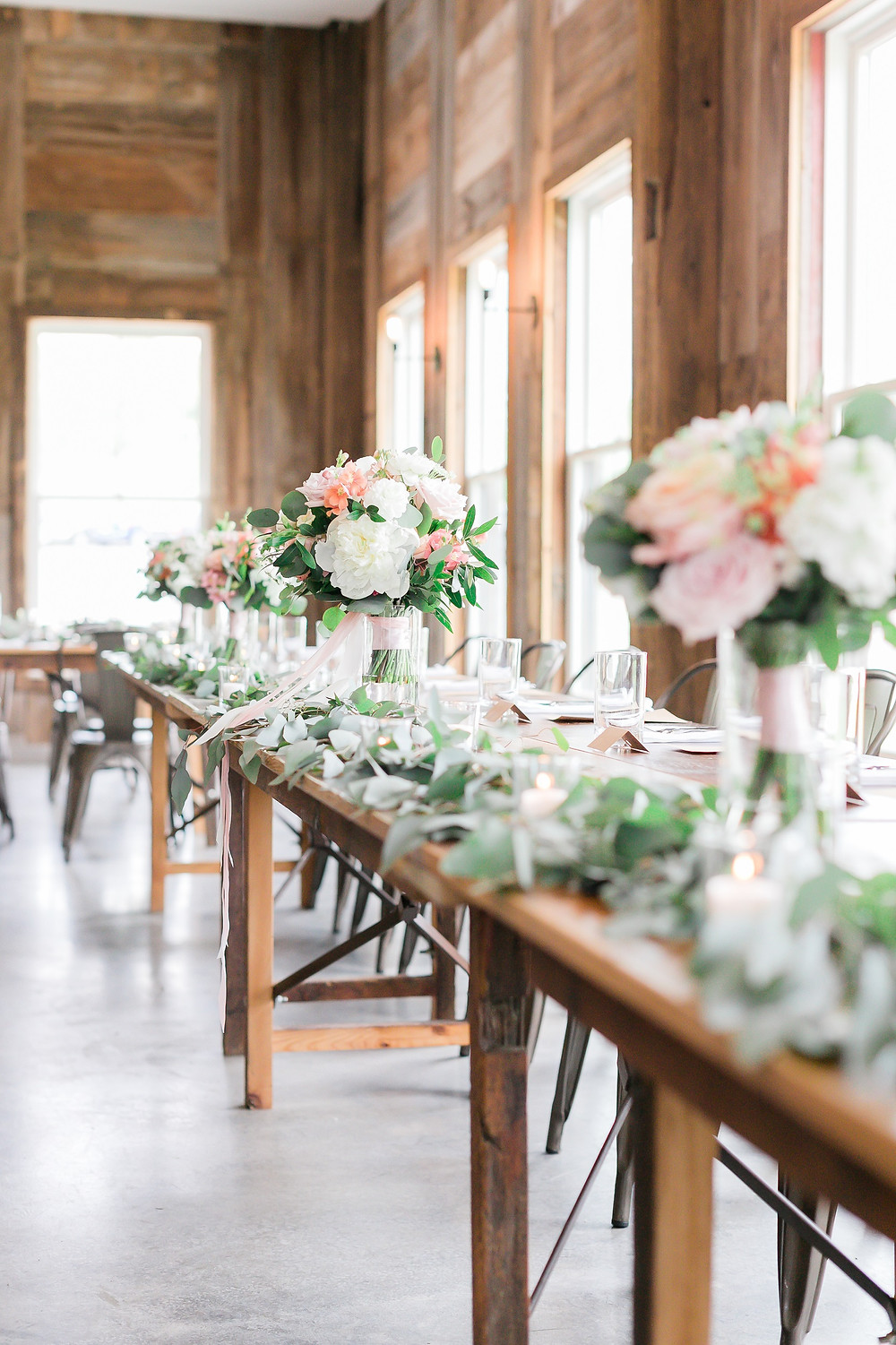 Head table at Rapid Creek Cidery with blush and peach wedding bouquets by Studio Bloom Iowa wedding florist Iowa City