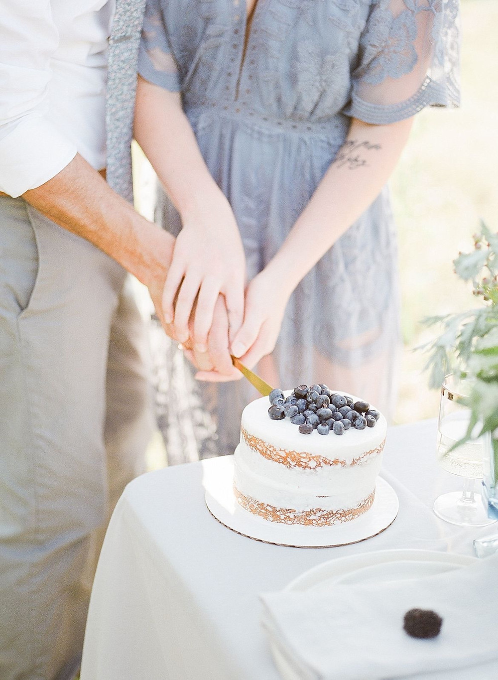 wedding anniversary couple cutting cake with blueberries