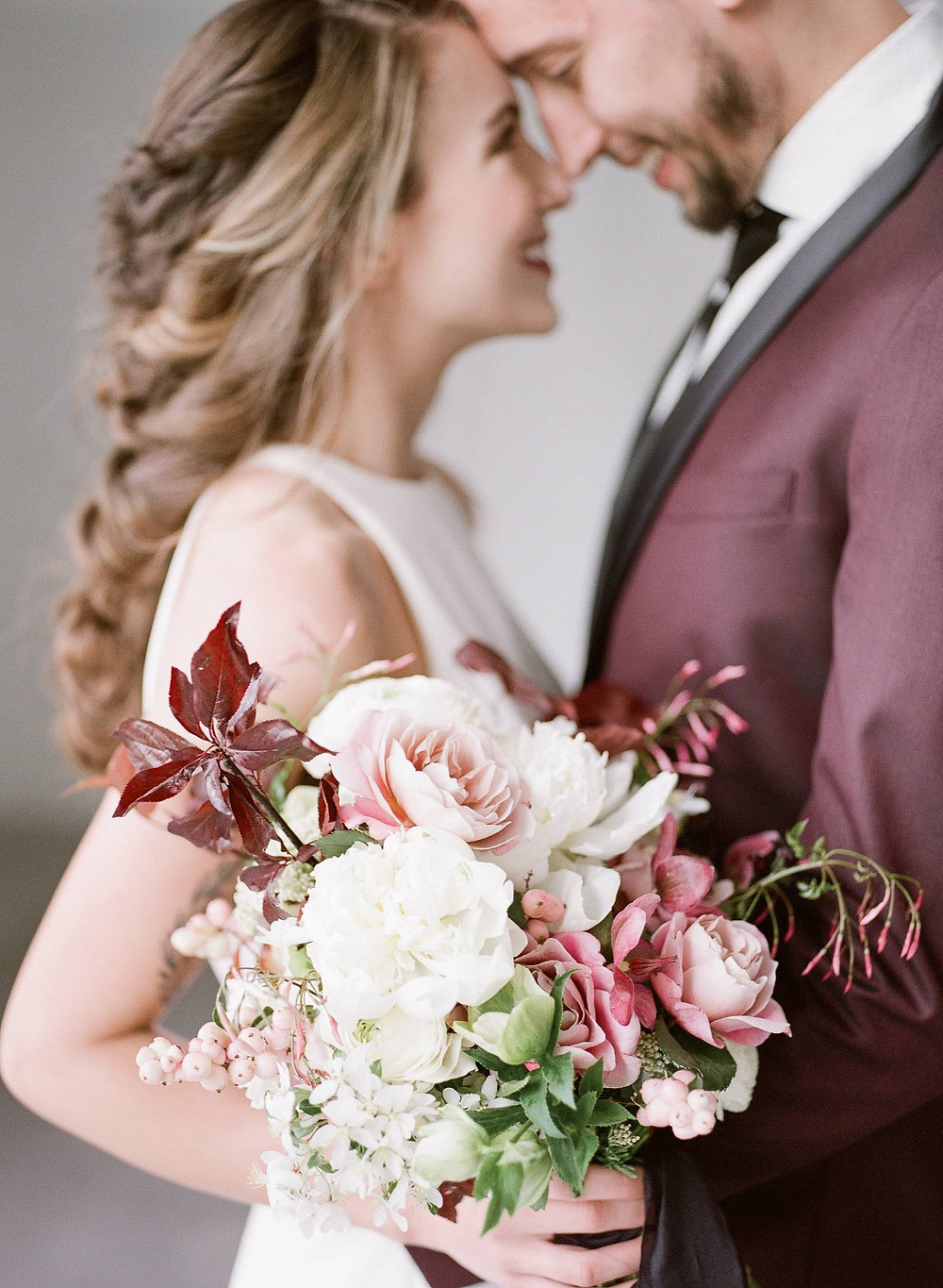 Modern bride and groom with Studio Bloom Iowa bridal bouquet of peonies, roses, ranunculus, hellebores, and plum branches