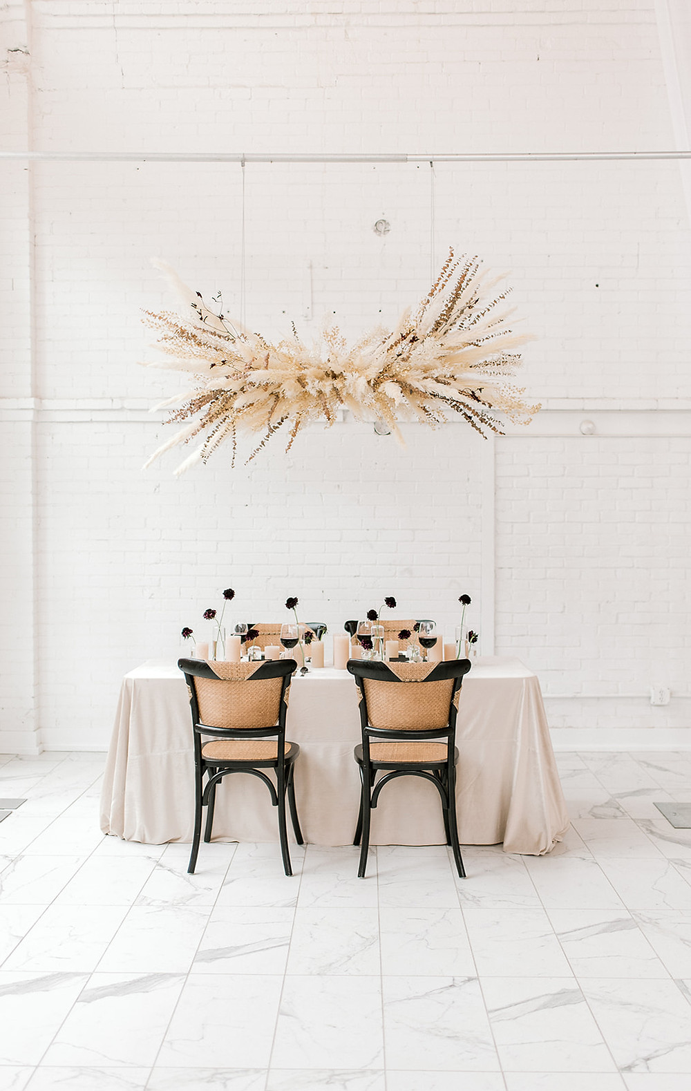 modern neutral minimalist wedding table in black and tan with hanging pampas grass arrangement by Studio Bloom Iowa