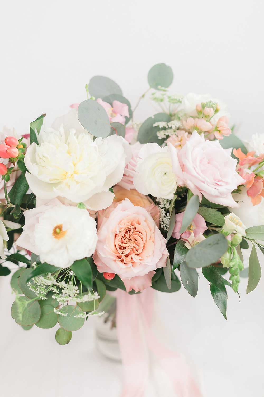 Studio Bloom Iowa bridal bouquet detail in pink and peach with peonies, roses, ranunculus, snapdragons, berries, and eucalyptus