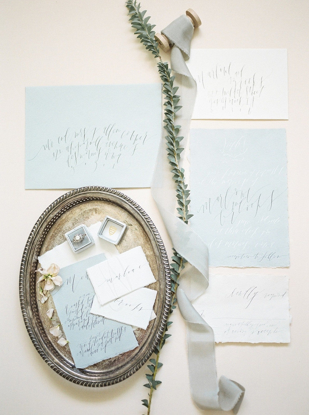 dusty blue beach wedding calligraphy hand torn invitation suite with ribbon and silver tray