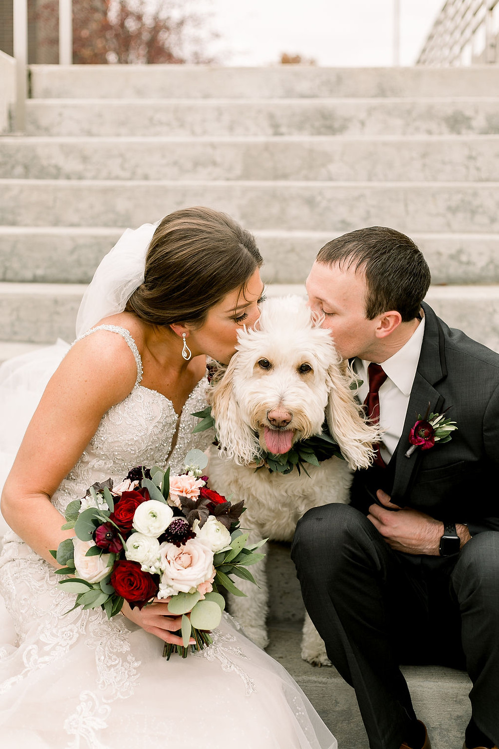 Bride and groom kissing dog in floral collar by studio bloom iowa cedar rapids wedding florist