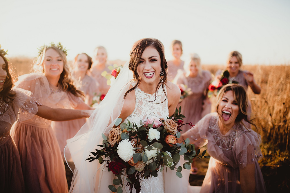 bride smiling in field holding bouquet by Studio Bloom Iowa in earthtones surrounded by happy bridesmaids in neutral dresses
