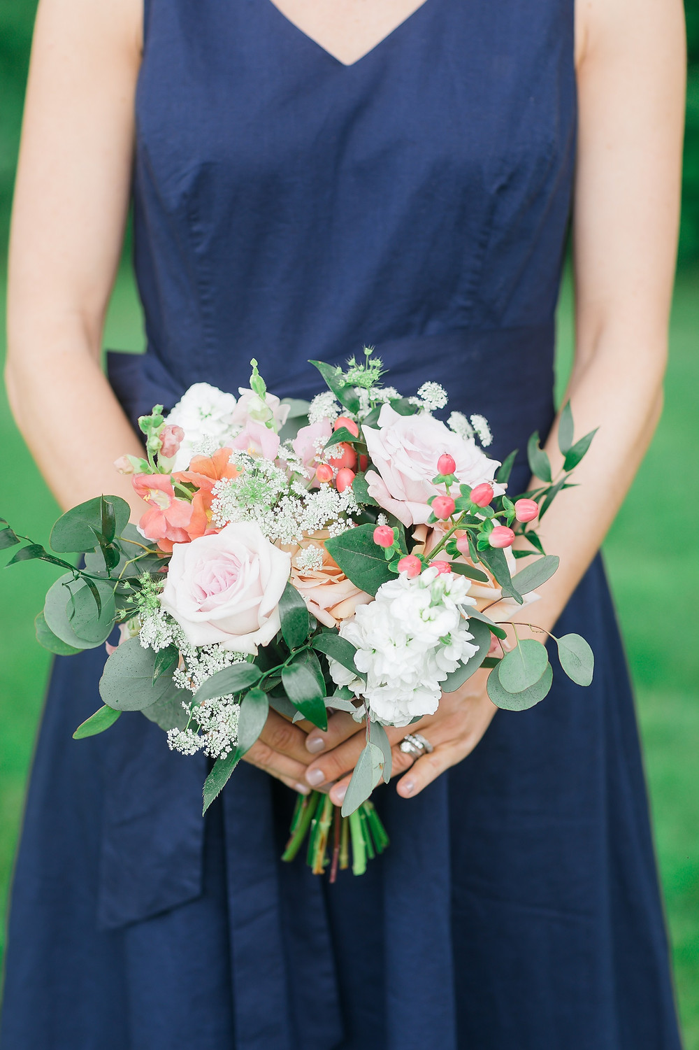 Bridesmaid in navy dress holding Studio Bloom Iowa bouquet in blush and peach with roses, queen annes lace, and berries
