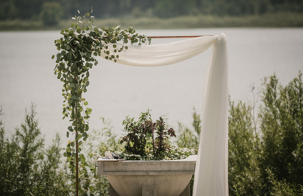 copper pipe arch with eucalyptus greenery and fabric by studio bloom iowa for a lakeside outdoor wedding ceremony