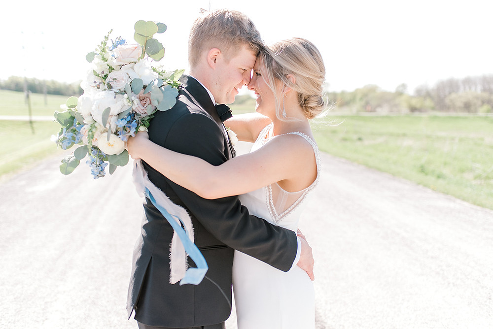 Bride and groom embracing on outside on dirt road holding blush and blue bridal bouquet by Studio Bloom Iowa wedding florist