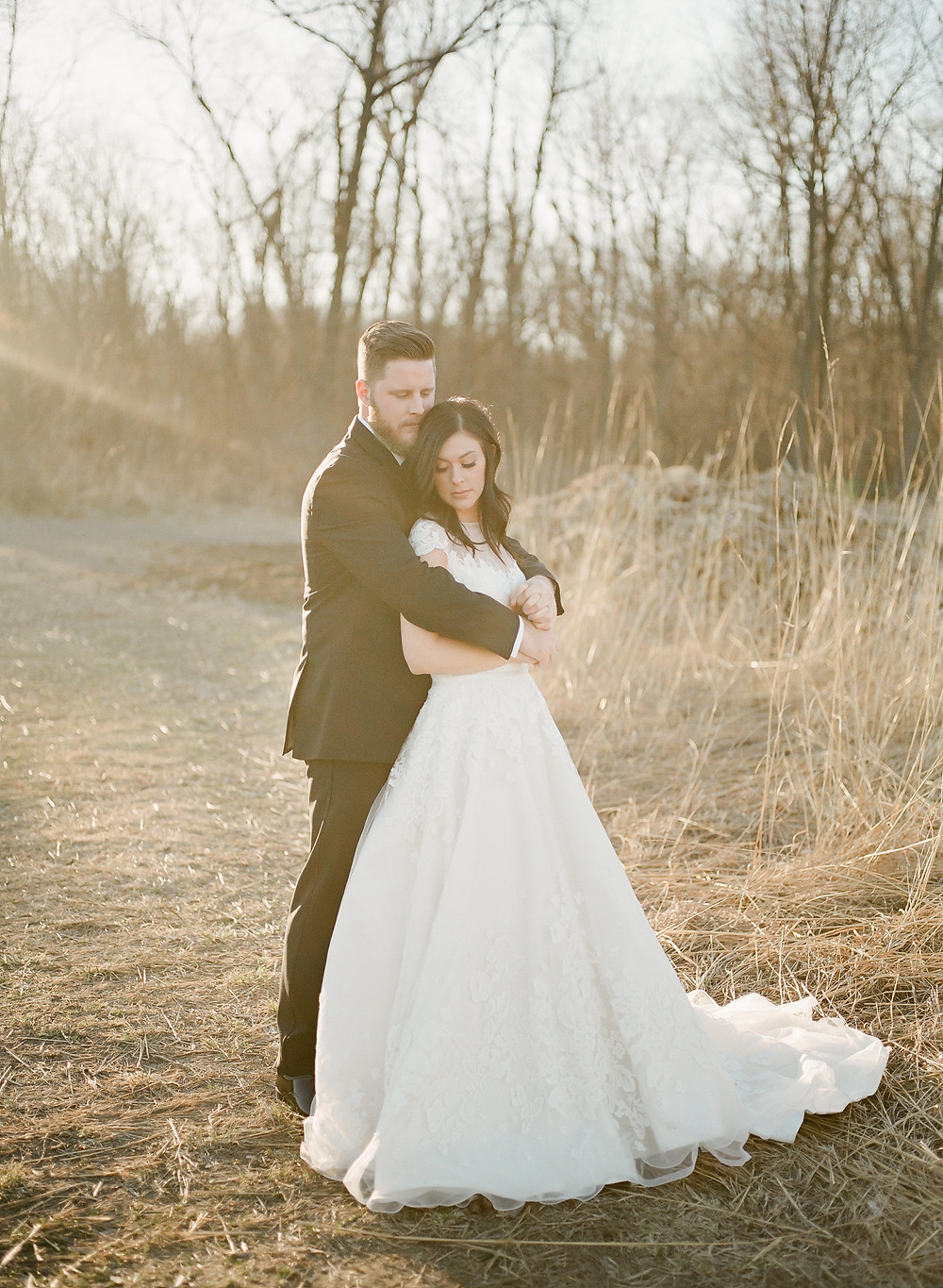 bride and groom embracing in winter field at sunset