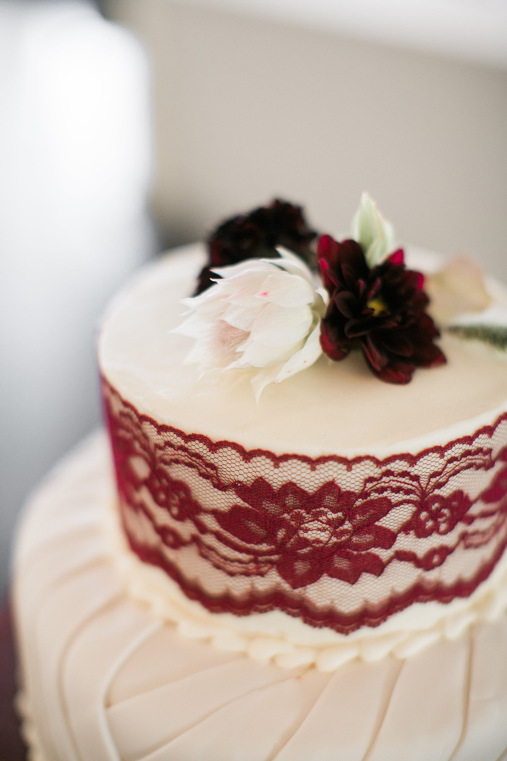 wedding cake with burgundy lace and dahlias and blushing bride on top