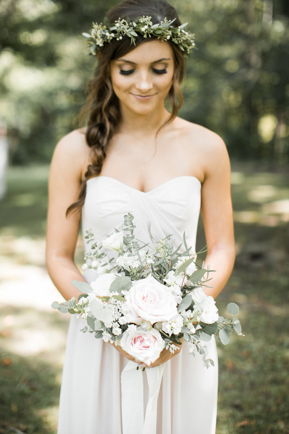 bridesmaid in blush dress wearing a greenery crown holding a bouquet by studio bloom iowa with roses and eucalyptus