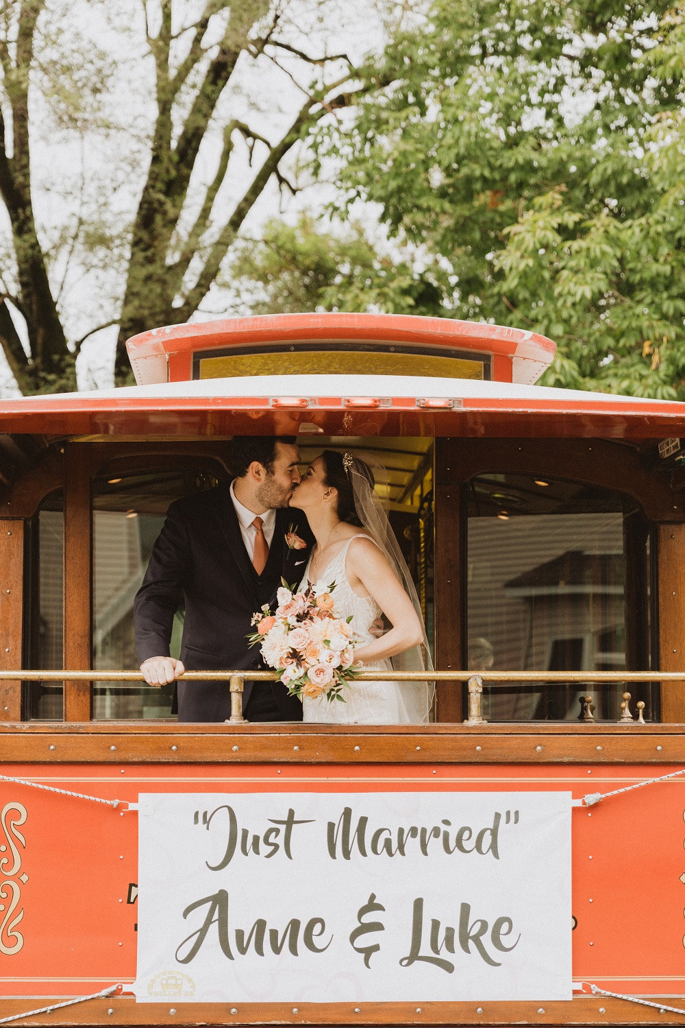 bride and groom kissing on back of trolley with wedding flowers by Studio Bloom