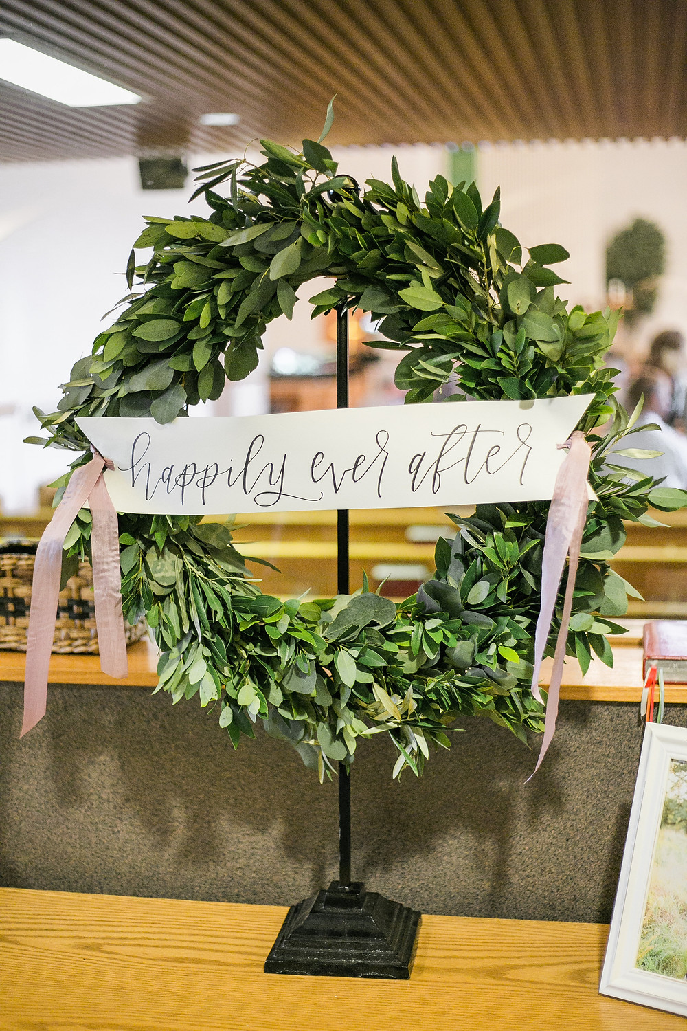 greenery wreath on stand with happily ever after banner for a wedding ceremony