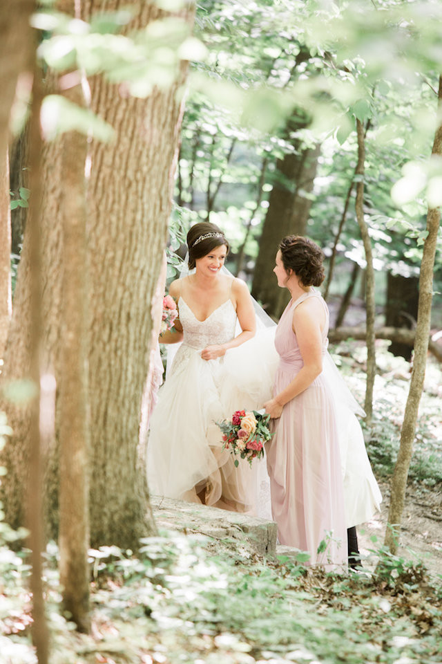 bride and bridesmaid in the woods walking to ceremony
