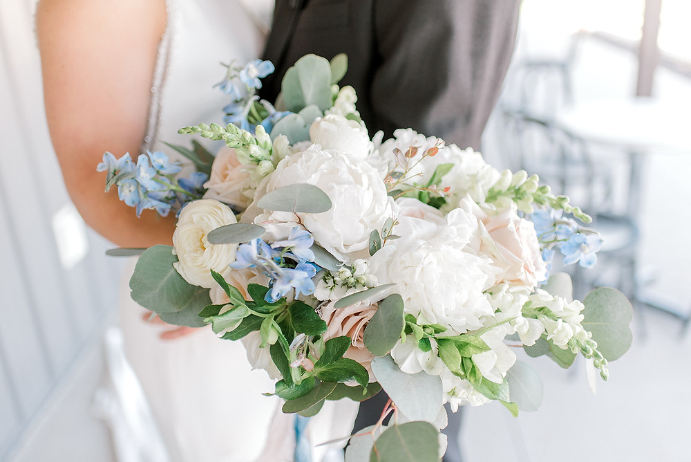 Bridal bouquet by Studio Bloom Iowa of white peonies, ranunculus, snapdragons, blush quicksand roses, and blue delphinium