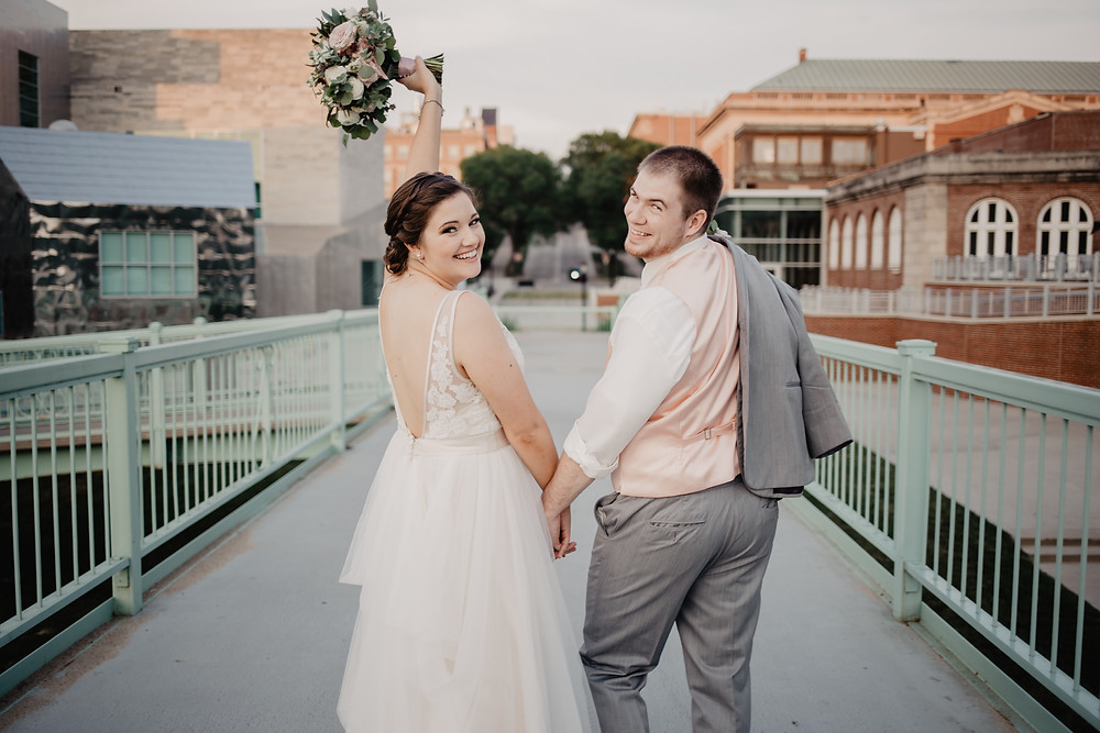 bride and groom waving from bridge in iowa city holding bridal bouquet