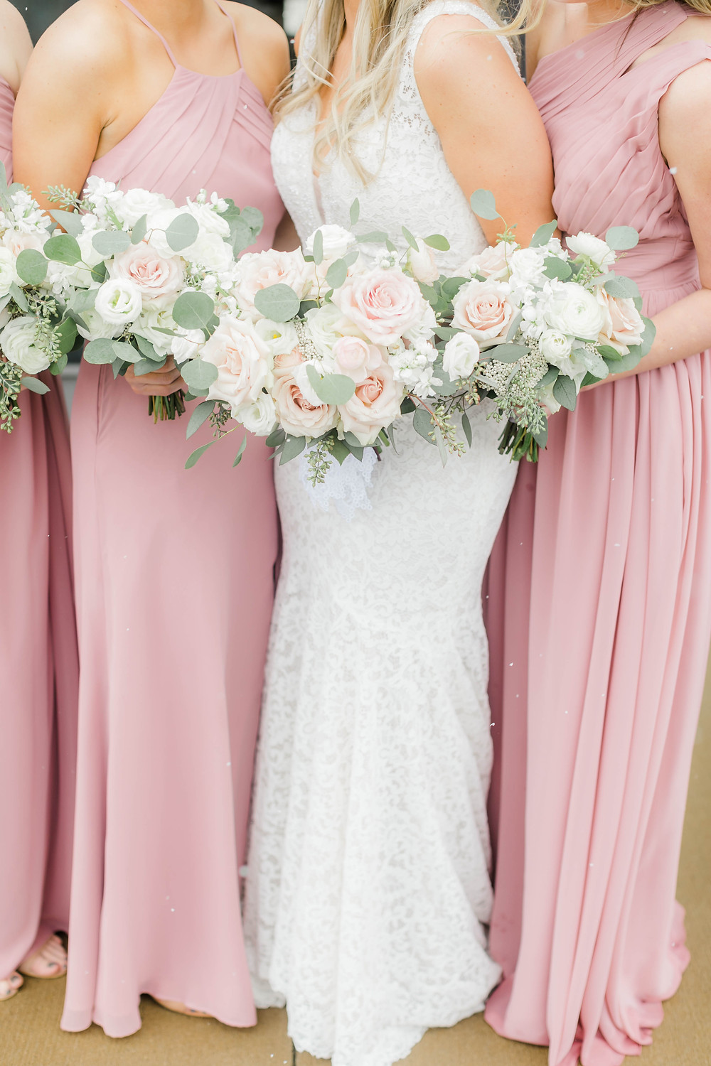 Bridal party with Studio Bloom Iowa bouquets of blush roses, ranunculus, lisianthus, stock, rice flower, and eucalyptus