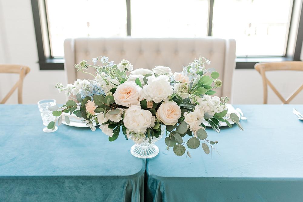 Lush centerpiece by Studio Bloom Iowa wedding florist of garden roses, peonies, delphinium, and eucalyptus on velvet linens