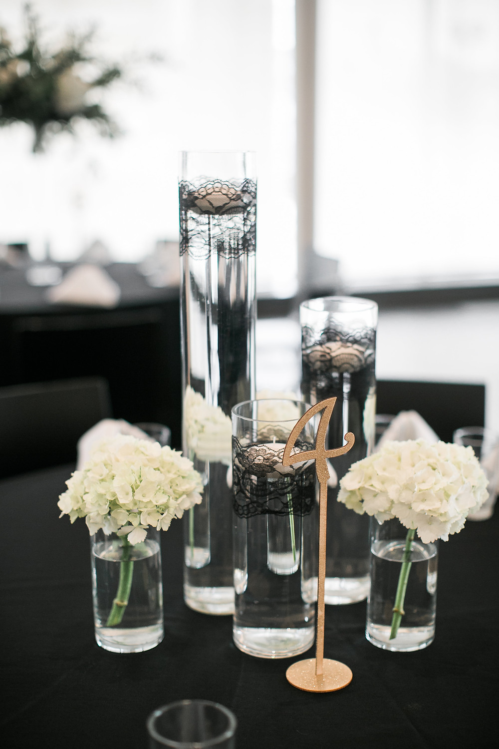 Tall cylinder vase trio centerpiece with floating candles ,black lace detail, and white hydrangea at eastbank venue