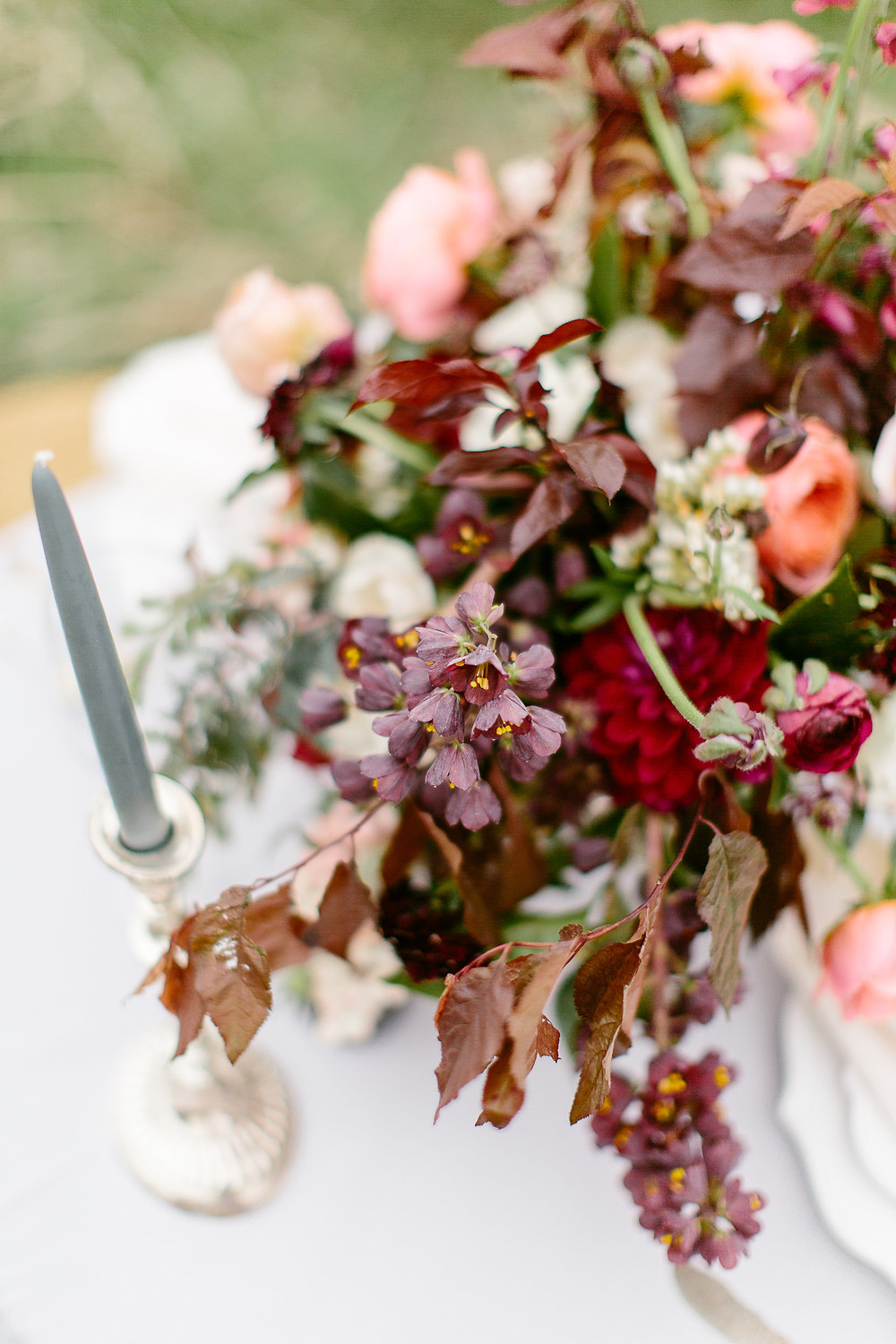 detail of burgundy wedding centerpiece with frittilaria, peonies, garden roses, ranunculus, and plum foliage