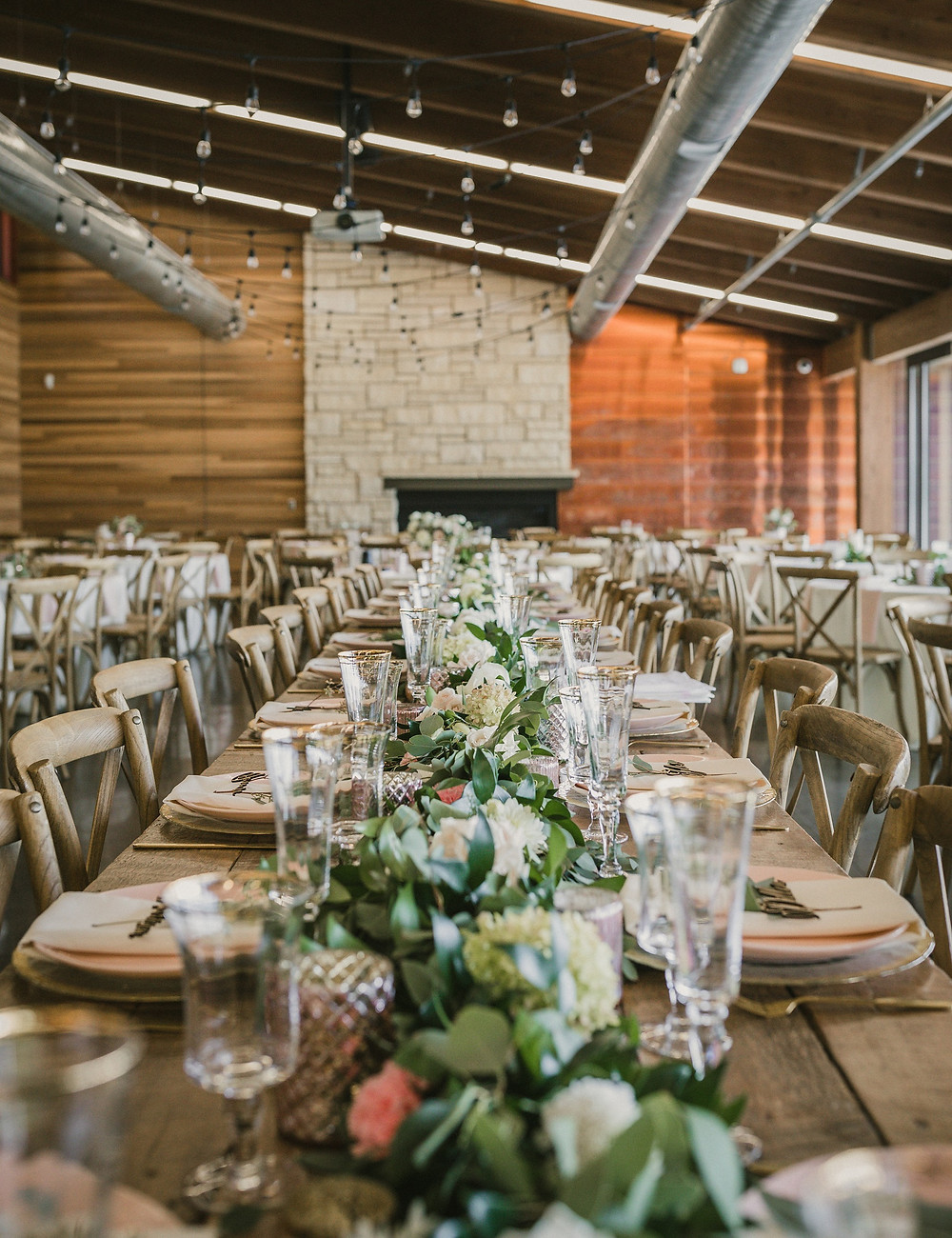 wedding reception at terry trueblood lodge in iowa city with greenery and flower garland by studio bloom iowa on a farm table