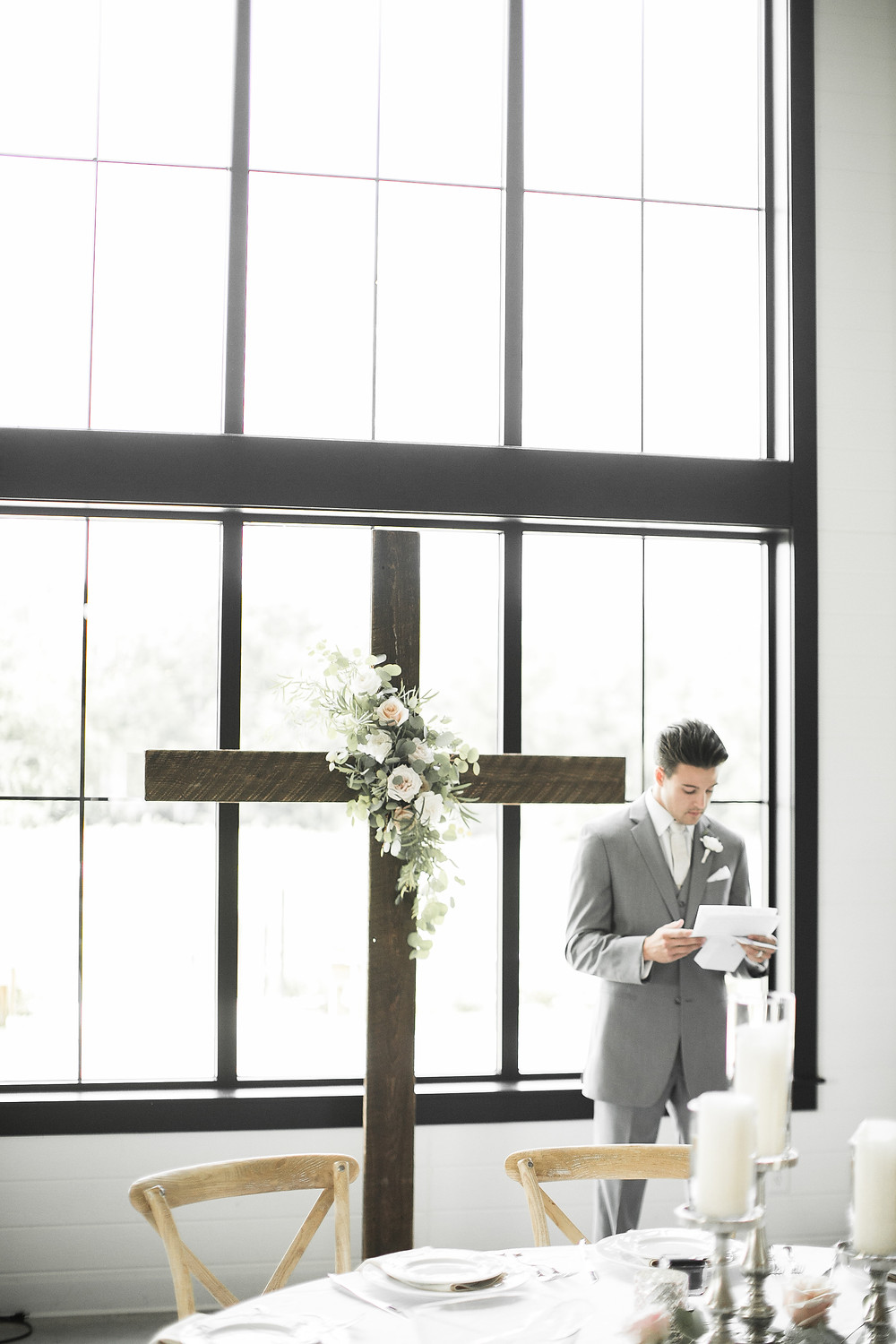 groom reading wedding day letter by wood cross with flowers by studio bloom iowa at ashton hill farm
